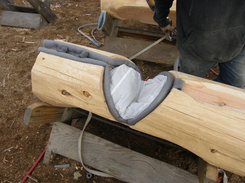 Batt insulation sealed in plastic envelope in log notch
